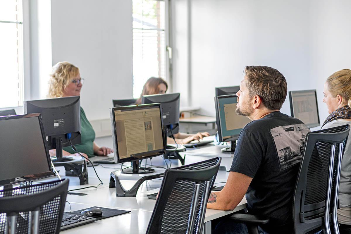 Foto von Menschen vor Computern bei einer Schulung