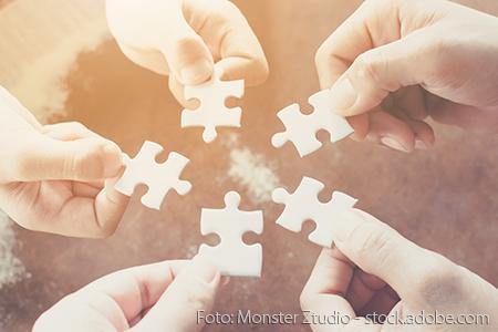 Hände die Puzzleteile halten